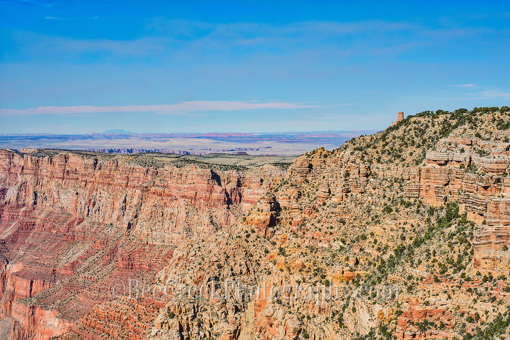 Grand view of the Watchtower from a distance as a very tiny spec, just barely visible and then your eye is drawn to the vista beyond and below  where it give way to the exposed rock below where erosion has formed the canyons as we know them today over millions of years.
