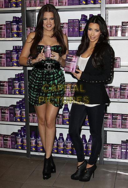 "KHLOE KARDASHIAN & KIM KARDASHIAN.At a photocall to introduce ""Quicktrim"" held At GNC Beverly Center, Los Angeles, California, USA,.15th October 2009..full length sisters family strapless green and black print dress waist belt tall short jacket leggings ankle boots heels ribbon woven silk satin white top bracelets holding product studs studded .CAP/ADM/KB.©Kevan Brooks/Admedia/Capital Pictures"