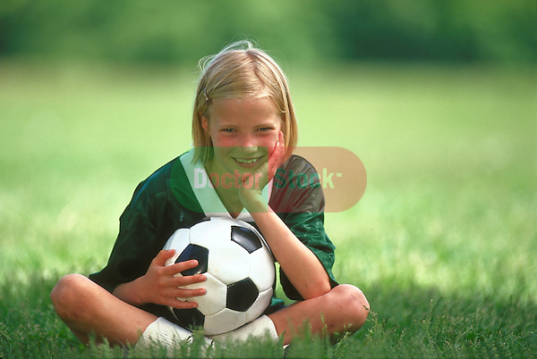 portrait of smiling girl in uniform sitting on grass with soccer ball