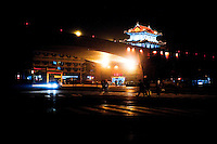 Evening landscape view of a Xī'ān chéngqiáng gate tower and commercial building signage on a street in the Xī'ān Shì Weiyang District in Shaanxi Province.  © LAN