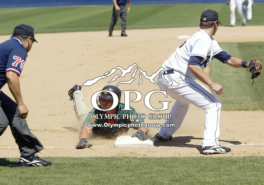 Fresno Grizzlies #28 Todd Linden slides head first into third base under third baseman Scott Youngbauer tag for a 2 RBI triple against Tacoma Rainiers at Cheney Stadium in Tacoma, Washington.