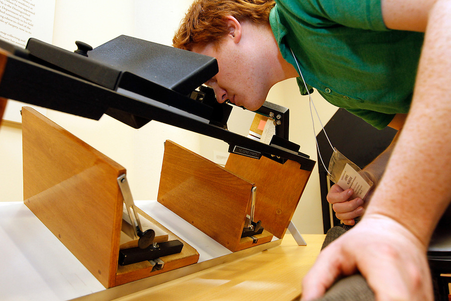 "Student James McBride views a book thru a Lindstrand Comparator machine during a Rare Book School summer camp class held at the University of Virginia in Charlottesville, Va. The compact Lindstrand Comparator uses two lenses to ""converge"" two texts into one, highlighting variations between the copies. Photo/Andrew Shurtleff"