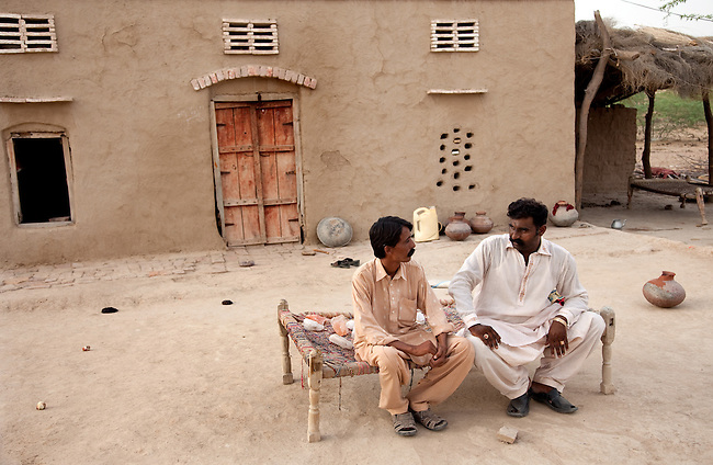 25 JULY 2011: Basti Mahraan Village, Punjab, Pakistan.    Mahar Abdul Latif (R), a former member of Muslim terrorist group Lashkar-i-Taiba (LeT) at his home village of Basti Mahraan in Pakistan with fellow villager Bachu Ram, a Hindu. After Ram offered to donate his rare blood type to save the life of a Muslim woman, relations thawed in the traditional violence between the Muslims and Hindu's of the village. The men are seated near a Hindu temple that was renovated by the Muslim's of the village in a sign of solidarity.Picture by Graham Crouch/Toronto Star