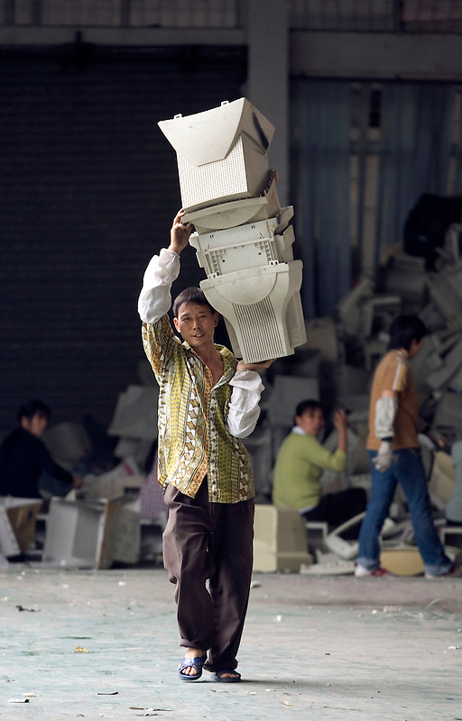 A migrant worker carries a stack of plastic computer screen casings, in a workshop specializing in recycling electronic trash in Panyu, China. Each year, between 20 and 50 million tons of electronic waste is generated globally. Most of it winds up in the developing world. Some of the most popular destinations for dumping computer hardware include China, India, and Nigeria. It can be 10 times cheaper for a ìrecyclerî to ship waste to China than to dispose of it properly at home. With the market for e-waste expected to top $11 billion by 2009, itís lucrative to dump on the developing world.