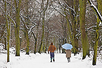 Winter scene as couple walk together across snow-covered Hampstead Heath, North London, United Kingdom