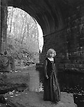 A young girl wearing a Gothic dress in a stone tunnel with a river beside her