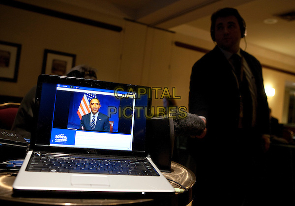 Reporters record United States President Barack Obama who is shown on the screen of a laptop computer as he speaks during a video teleconference with Iowa Caucus attendees from Washington, D.C. on Tuesday, January 3, 2012.  .CAP/ADM/JR.©Joshua Roberts/Pool/CNP/AdMedia/Capital Pictures.