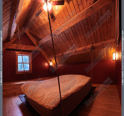 Attic loft bedroom with a hanging bed in a Canadian timber frame country house, interior with a lot of wood, Muskoka, Ontario, Canada