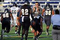 30 March 2012:  FIU Football Head Coach Mario Cristobal encourages his players as they run through drills prior to the FIU Football Spring Game at University Park Stadium in Miami, Florida.