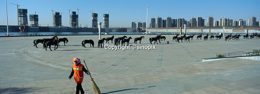 A cleaner works in in front of one hundred bronze horse bronze near the artificial river in Kangbashi district of the Chinese city of Ordos, Inner Mongolia. 12-May-2011