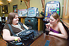 Woman with a disability chatting with non disabled friend out at the pub,