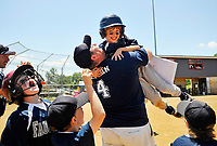 After getting the game winning hit in the bottom of the last inning to win the game, 8-year-old Cole Western leaps into his dad Matt Western's arms as his dad and the whole team rushed out onto the field to celebrate the Fauquier Gators dramatic 14-13 win in their Cal Ripkin League district playoff game.
