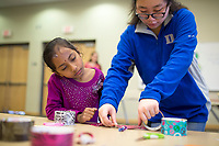 """NWA Democrat-Gazette/CHARLIE KAIJO Vanessa Tam (from right) helps Samsitha Reddy, 6, of Bentonville make a bookmark during the """"How-To"""" festival, Saturday, March 24, 2018 at the Bentonville Library in Bentonville. <br /><br />Participants learned how to create a Duck Tape® corner bookmark, design a balloon rocket racer, discover finger knitting, write a Haiku poem, paint a watercolor masterpiece and learn about BookFlix®"""