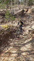 """NWA Democrat-Gazette/FLIP PUTTHOFF <br /> Bob Cable of Fayetteville, a group ride leader, rolls through the """"gravity cavity"""" along the Fossil Flats Trail. Cable has been a ride leader at the festival for most of its 31 years."""
