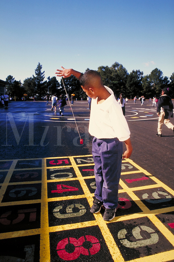Recess at Carl Munck Elementary School. Playground activities. Playing with yo-yo. Oakland, California.