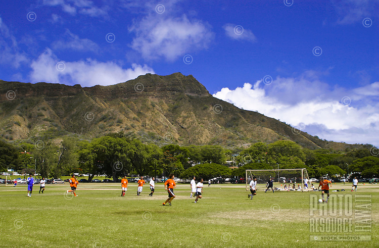 Young soccer players compete on the open fields of Kapiolani Park near scenic Diamond Head,Oahu.