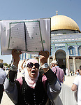 A Palestinian woman holds up a copy of Holy Qur'an during a demonstration against the controversial film 'Innocence of Muslims' in front of al-Aqsa Mosqe in Jerusalem, on September 14, 2012. The controversial low budget film reportedly made by an Israeli-American which portrays Muslims as immoral and gratuitous, sparked fury in Libya, where four Americans including the ambassador were killed on Tuesday when a mob attacked the US consulate in Benghazi, and has led to protests outside US missions in Morocco, Sudan, Egypt, Tunisia and Yemen. Photo by Mahfouz Abu Turk