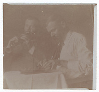 14b.<br /> <br /> 2 1/4  x  2 7/16  [sepia]<br /> <br /> (double) Sam Crone, dressed differently in each pose; playing musical duet at small table; frontal figure, in smock, playing a clarinet, left; figure in profile, in white shirt and wide tie, looking down while playing autoharp, right.