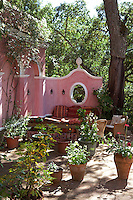 A shady seating area in a corner of the courtyard garden against a pink wall