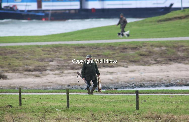 Foto VidiPhoto<br /> <br /> OCHTEN - Hinderlijke hazen. Jagers van de wildbeheereenheid (WBE) Nederbetuwe zijn maandag in de uiterwaarden van Ochten in Gelderland op pad om de hazenstand rond de eigendommen van boomkwekers en fruittelers terug te dringen. Op dit moment worden overal jonge boompjes en struiken aangeplant. Hazen zijn dol op de jonge loten, met enorme schade voor telers en kwekers als gevolg. Jagers hebben als taak schade door wild te bestrijden. Haas is bovendien een populair stukje vlees met Kerst.