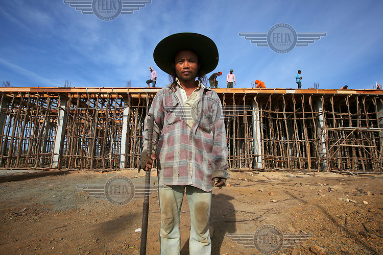 Construction worker Abdul on a building site next to a newly constructed road in Banda Aceh. The building of the new road has brought a great deal of employment for Acehnese people with new shops, business and housing being constructed.