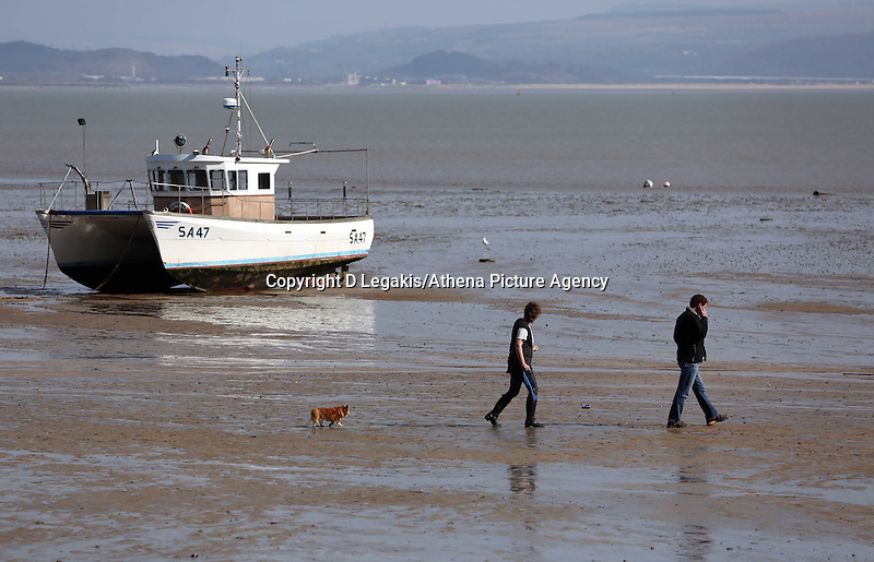 WEATHER PICTURE WALES<br /> Pictured: A couple with their dog enjoy a stroll on the wet snad while the tide is out in sunny but cold weather on Mumbles beach, near Swansea, south Wales. Saturday 15 March 2014<br /> Re: Sunny weather experienced in many parts of the UK.