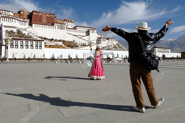 A photographer working his spot in front of the Potala Palace in Lhasa guided a visitor, whom had dressed in traditional Tibetan costume from amongst his props, how to pose for her commemorative picture. November 19, 2006
