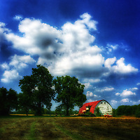 Blue skies and clouds over a cut hay field and barn at the Braun Farm in Westerville, Ohio.