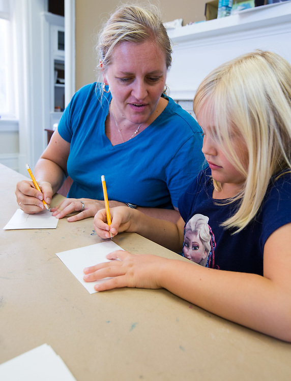 Ella Kuchnick, 6, and her mother Shannon Kushnick draw their own stamps at the Sunday Family Art Encounters at the Kennedy Museum of Art.