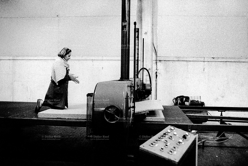 Italy. Marche Region. Pesaro. Strappazzini company. Polyurethane plant. A woman worker warms her hands while on her knees. Polyurethane cut out from cars seats are recycled and cut in slides to make new materials as cars carpets underlays. © 1993 Didier Ruef