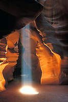 Dramatic shaft of light beam in a golden cavern in Upper Antelope Canyon near Lake Powell in Page, Arizona,  Navajo Nation tribal park