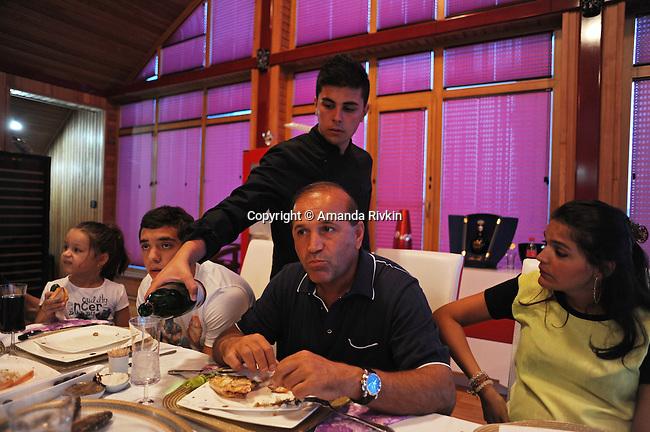 Ibrahim Ibrahimov (center) sits at the dinner table with his granddaughter Cahan Guliyeva, 4, son Huseyn Ibrahimov, 18, and daughter Ilkana Ibrahimova, 22, in his home between Sangachal and Sahil, Azerbaijan on August 16, 2012.