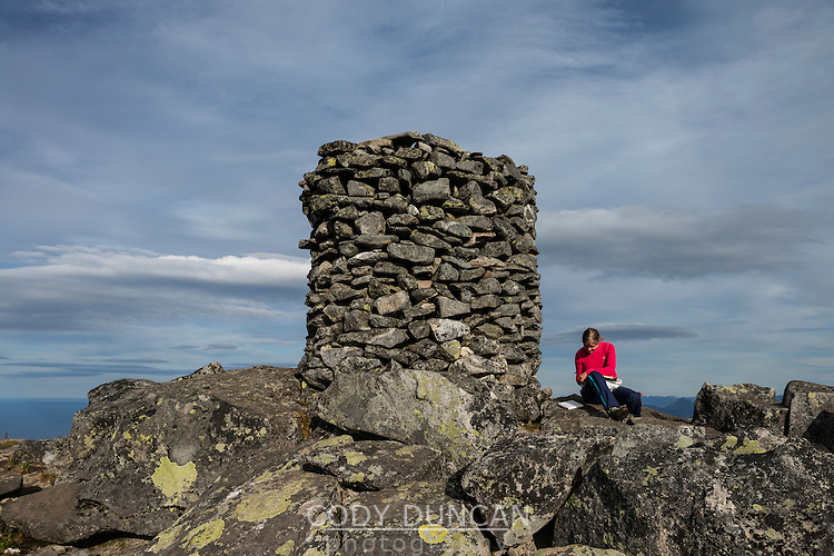 Female hikers sits next to large summit cairn on Matmora mountain peak, Austvågøy, Lofoten Islands, Norway