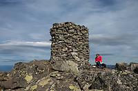 Female hikers sits next to large summit cairn on Matmora mountain peak, Austvågøy, Lofoten Islands, Norway