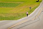 Woman walking along country road.