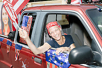 A supporter of Democratic presidential candidate and Hawaii representative (D-HI 2nd) Tulsi Gabbard waves a flag from a pickup truck in the 4th of July Parade in Amherst, New Hampshire, on Thu., July 4, 2019.