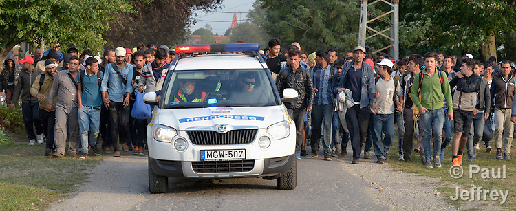 Carefully shepherded by police, refugees and migrants walk through the Hungarian town of Hegyeshalom on their way to the border where they will cross into Austria. Hundreds of thousands of refugees and migrants flowed through Hungary in 2015, on their way from Syria, Iraq and other countries to western Europe.