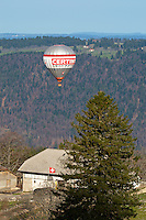 Hot air balloon flying low over a farm in the Jura mountains