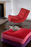 The floor cushions have been chosen to complement the bright red of the 60's style armchair next to the fireplace