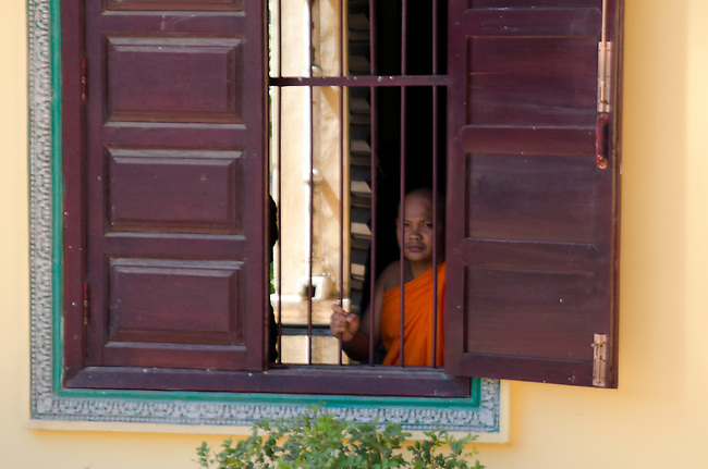 Buddhist monk looking out temple window