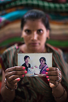 "Sharda Solanki, 36, holds up a photograph of Dr. Nayana Patel and the twins she had for an Asian client, as she sits in her house in Anand, Gujarat, India on 9th December 2012. While her husband Kantibhai works as a security guard earning 5000 rupees per month, Sharda had made hundreds of thousands with 2 surrogacies that she did with Akanksha Clinic, instantly changing her family's lives and future. ""Dr. Patel is a blessing for everyone, both parties. For us who had nothing, and others who had no children. She changed our lives."" Photo by Suzanne Lee / Marie-Claire France"