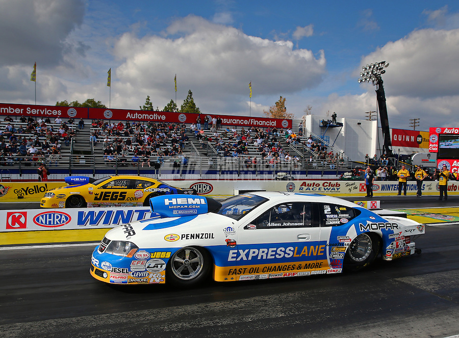 Feb 7, 2014; Pomona, CA, USA; NHRA top pro stock driver Allen Johnson (near lane) races alongside Jeg Coughlin Jr during qualifying for the Winternationals at Auto Club Raceway at Pomona. Mandatory Credit: Mark J. Rebilas-