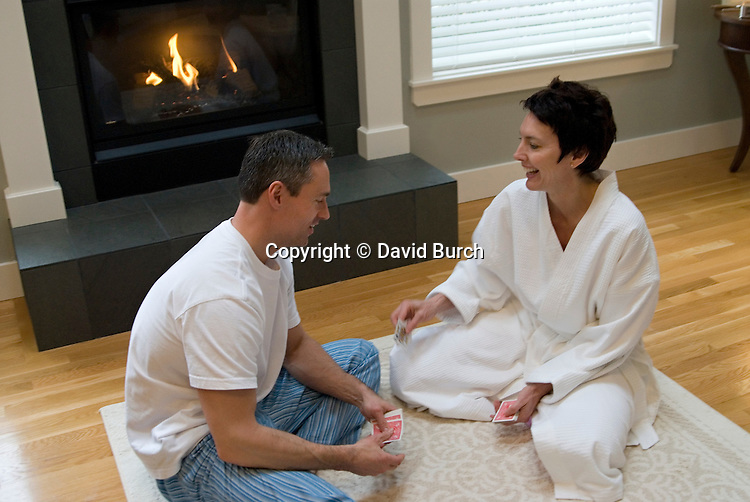Mature couple playing cards near fireplace