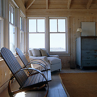 The clapboard interior of this simple beach house is sparsely furnished and has windows overlooking the dunes