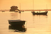 USA, Jamestown, RI - Dinghy floats by the the Clingstone house on the rock, golden sunrise.