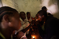 """Joanette, 22 years old ( on left ), waits for her turn to inhale the """"brown brown"""", a mixture between cocaine and gunpowder while the others score  in an abandoned compound   in Monrovia, Liberia on  Wednesday March 21 2007..Melvin, 29 AKA """"Dad"""",  John, 29 AKA """"Desperate Soldier, Thomas 28 AKA """"Bullet Patrol"""", Leroy, 28, AKA """" Pussy Mechanic"""" and Steven 27 AKA """"Field Marshall"""" are all former child soldiers that found each other on the streets after the last round was fired in Liberia. Since then they """"Hustle"""" to put some food in their stomachs and buy some drugs to """" make them forget about their lives""""..ALL NAMES HAVE BEEN FICTIONALIZED TO PROTECT THE IDENTITIES OF THE 5 MEN."""