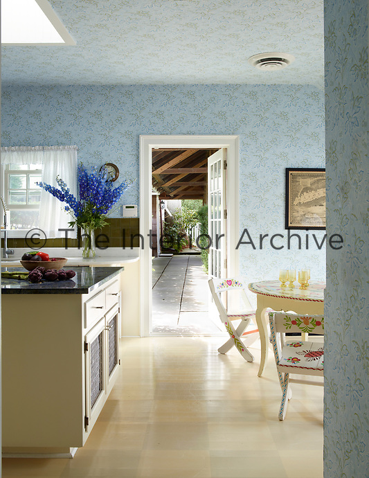 The kitchen is decorated in blue pattern wallpaper and the table and chairs are painted with hearts and flowers in the style of folk artist Peter Hunt.