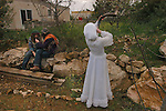A woman blows a ram's horn next to her fellow settlers, during a party for the Jewish holiday of Purim, in the Israeli settlement of Elazar, West Bank.