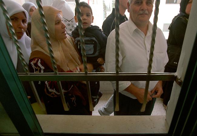 Medizinische Hilfe fuer Palaestinenser<br /> Seit Oktober 2000 ist die palaestinensische Stadt Bedia nahe Nablus nicht mehr von Israel per Auto zu erreichen. Von der israelischen Regierung aufgeschuettete Strassensperren sind fuer Fahrzeuge jeglicher Art unueberwindbar geworden. In der 10.000 Einwohnerstadt mangelt es an nahezu allem. Medizinische Versorgung gab es letztmals im Maerz diesen Jahres.<br /> Die rund 500 Mitglieder zaehlende israelisch-palaestinensische Menschenrechtsorganisation Physicians for Human Rights (PHR) hat nach einem Hilferuf des palaestinensischen Roten Kreuzes im Rathaus von Bedia eine medizinische Versorgung der Bevoelkerung durchgefuehrt (Medical Day). Rund 600 Personen konnten von 11 Aerzten und etlichen Krankenschwestern nach bis zu acht Stunden Wartezeit behandelt werden. Die Mediziner mussten an diesem Tag die dreifache Menge an Menschen versorgen. Die Patienten kamen zum Teil aus bis zu 35 km Entfernung. Das Gesundheitssytem in den palaestinensichen Autonomiegebieten ist nach Angaben der PHR seit dem Beginn der &quot;Operation Schutzschild&quot; kollabiert. Die meisten der erkrankten Kinder leiden an Atemwegs- und Viruserkrankungen.<br /> Die PHR existieren seit der ersten Intifada 1988 und haben sich zum Ziel gesetzt, in den palaestinensischen Gebieten ohne Ansehen der Herkunft und Zugehoerigkeit medizinische Hilfe zu leisten. Fuer schwer und chronisch Erkrankte versuchen die PHR-Mitarbeiter Transporte und klinische Versorgung in israelische und us-amerikanische Hospitaeler zu ermoeglichen. Bis auf zwoelf Hauptamtliche arbeiten alle anderen Mitglieder ehrenamtlich. Die Organisation finanziert sich durch Geld- und Sachspenden. Eine Zusammenarbeit mit israelischen Gesundheitsinstitutionen wird von Regierungsseite abgelehnt.<br /> Hier: Die hilfsbeduerftigen Menschen warten vor einem der Behandlungsraeume.<br /> Bedia / Israel, 18.05.2002<br /> Copyright: Christian-Ditsch.de<br /> [Inhaltsveraendernde Manipulation des Fotos nur nach au