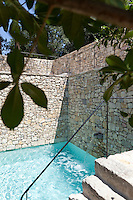 A textured wall of provencal stone encloses this courtyard swimming pool